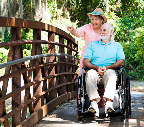 woman-pushing-man-in-wheelchair-across-bridge-enjoying-scenery