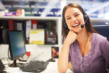 smiling-woman-sitting-at-desk-wearing-telephone-headset-with-her-hand-at-chin