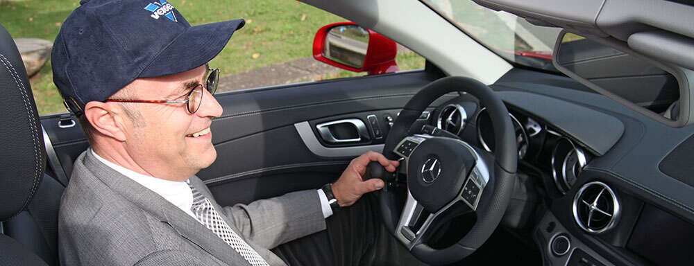smiling-man-sitting-in-driver's-seat-of-vehicle-using-steering-knobs