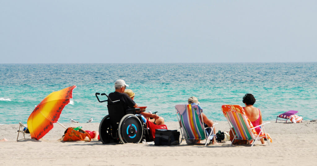 Group of people at the beach one in a wheelchair