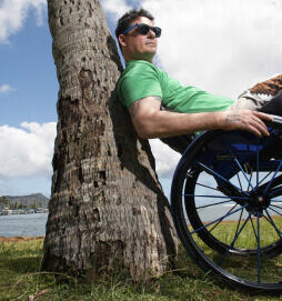 man in wheelchair leaning against tree