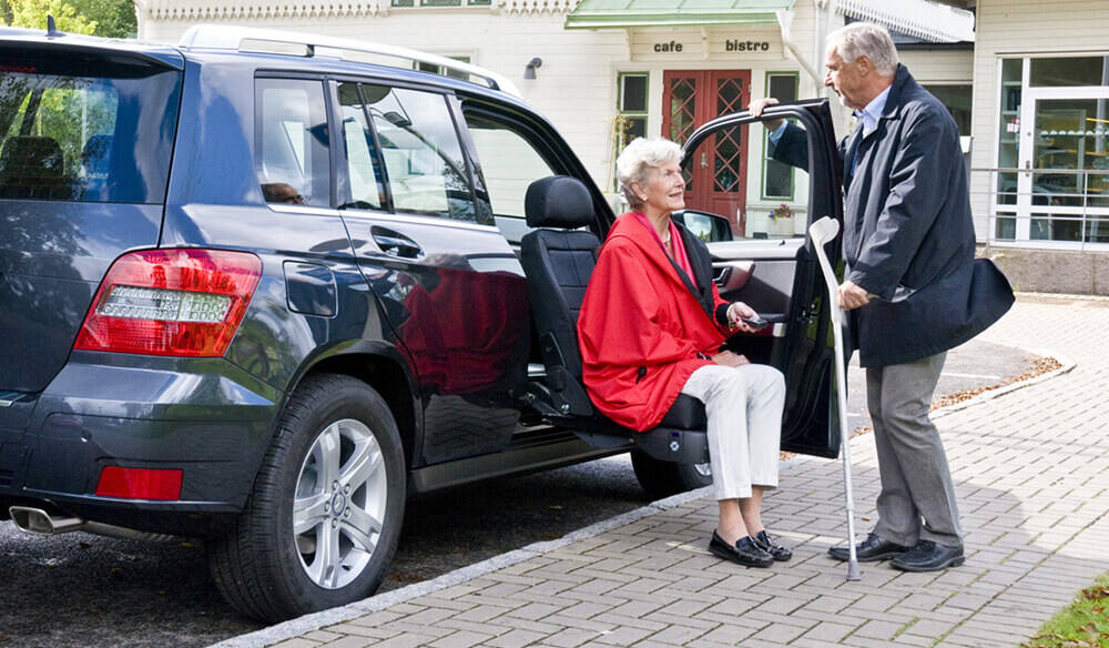 woman getting out of a blue vehicle using a turning seat with man holding door for her
