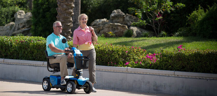 man on blue electric mobility scooter with woman walking outside