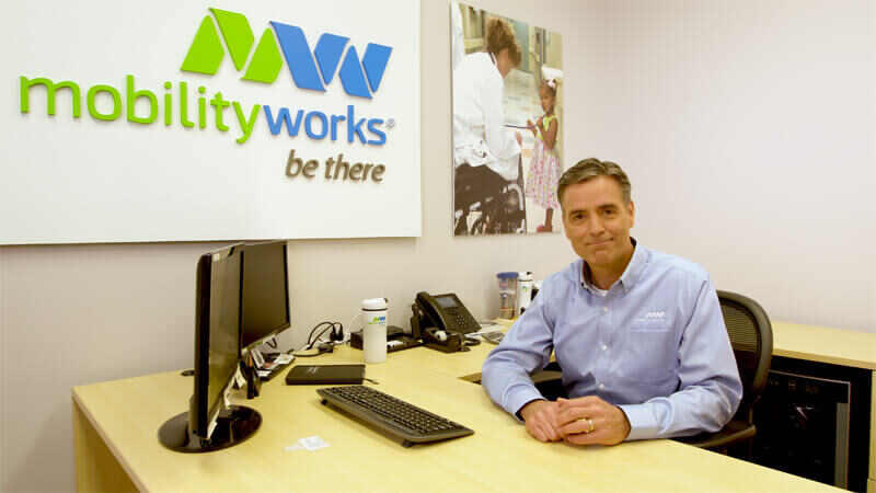 man in MobilityWorks shirt sitting at a desk