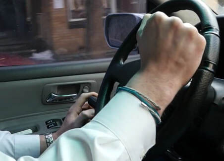 hands on a spinner wheel on a vehicle steering wheel