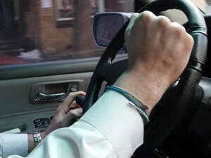 person using a spinner knob attached to steering wheel