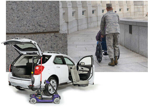 White SUV with scooter lift and turning seat in front of veteran pushing person in wheelchair at war memorial