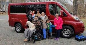 Family standing in front of red wheelchair van