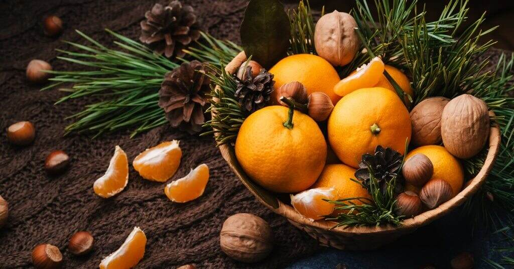 Tangerines, walnuts and hazelnuts decorated with pine cones and branches