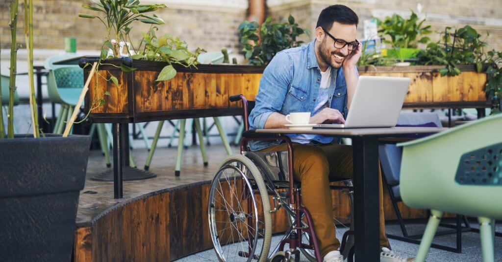 man in wheelchair at outdoor cafe on a computer