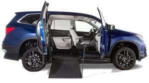 Small image of sapphire Honda Pilot wheelchair van with passenger side doors open and newly deployed manual ramp