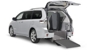 Small image of an angled view of a silver wheelchair van with a rear manual ramp