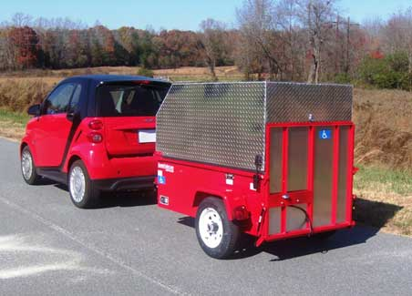 small red vehicle pulling a red ScootaTrailer