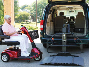 elderly lady driving red scooter onto wheelchair lift on back of minivan