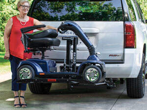woman with scooter on lift on back of white SUV