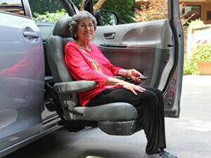 elderly lady sitting in a turning automotive seat that is lowering out of the vehicle