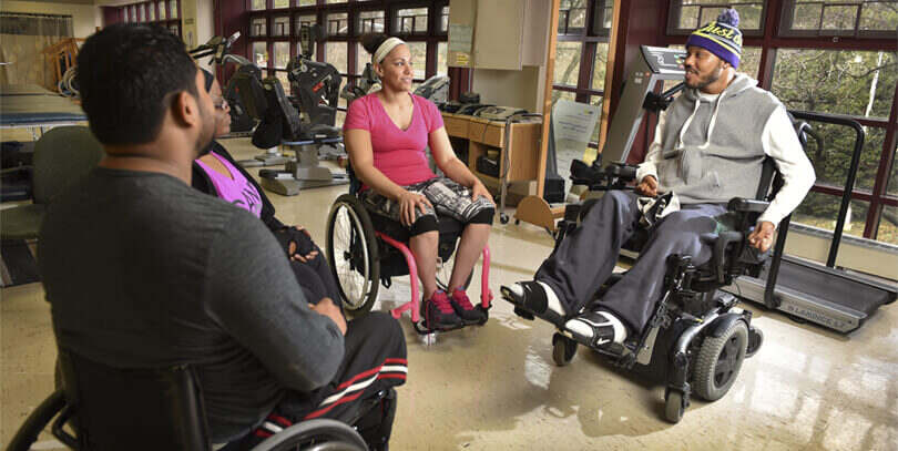 people in wheelchairs in a gym setting