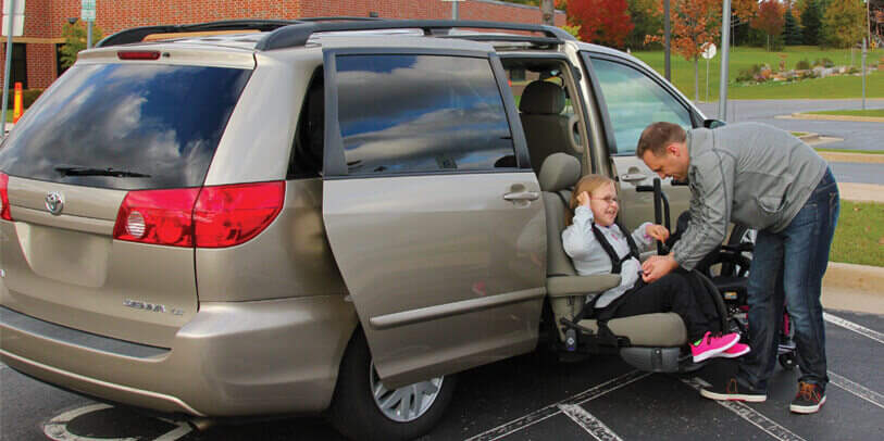 Man putting a child into a turning seat in a van