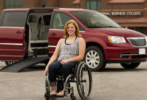 Women in a wheelchair in front of a red Chrystler wheelchair van with the side entry door open