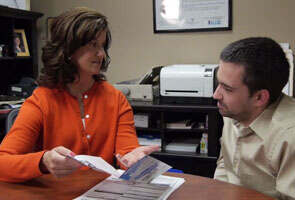 Female consultant helping man with wheelchair van financing in an office