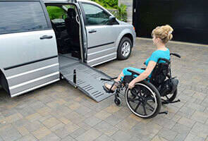 woman in wheelchair using a powerpull ramp assistant to enter a wheelchair van with a side entry ramp