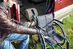 person using Adapt Speedy Lift to retrieve a wheelchair from back seat of vehicle
